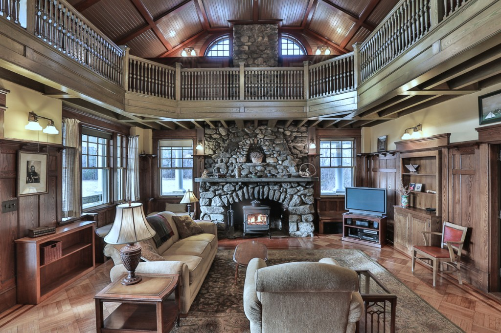 The Great Room with stone fireplace, wooden paneling and bannister surrounding